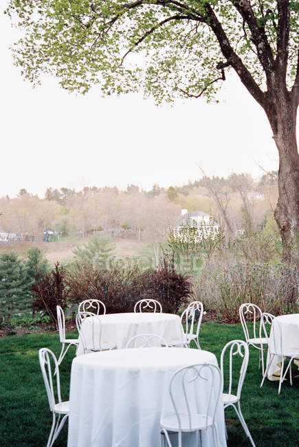 Tables and chairs set with white table clothes — Stock Photo