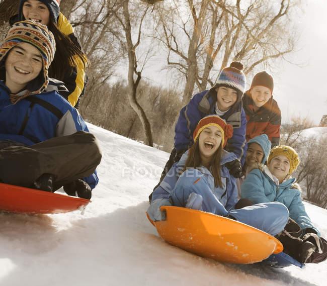 Kinder auf Schlitten im Schnee. — Stockfoto
