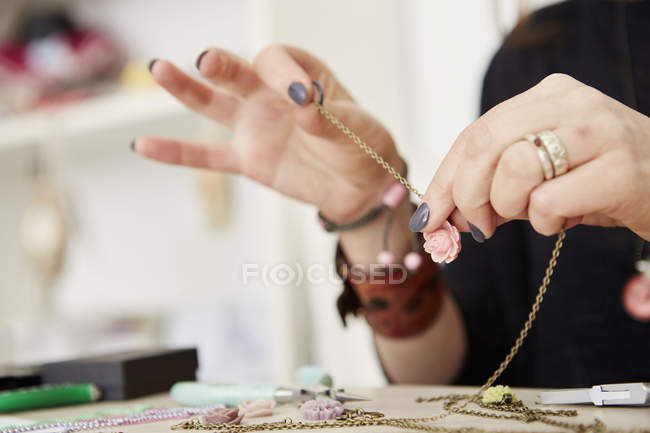 Woman seated at workbench holding gold chain — Stock Photo