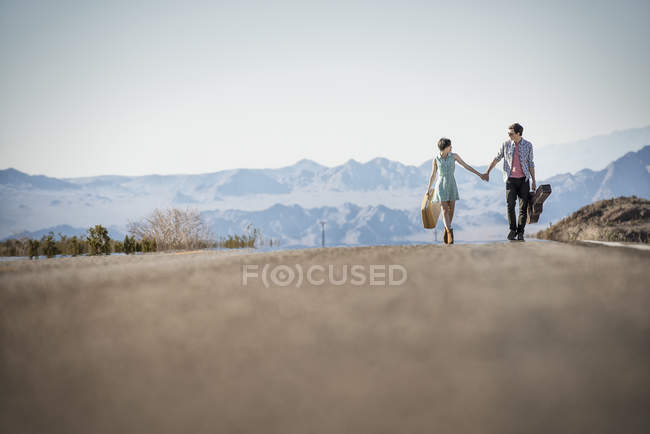Couple on a tarmac road in desert — Stock Photo