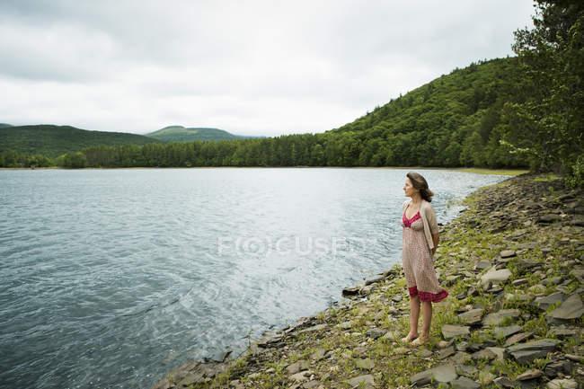 Mujer por un lago de montaña - foto de stock