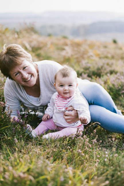 Femme assise sur le sol avec bébé — Photo de stock