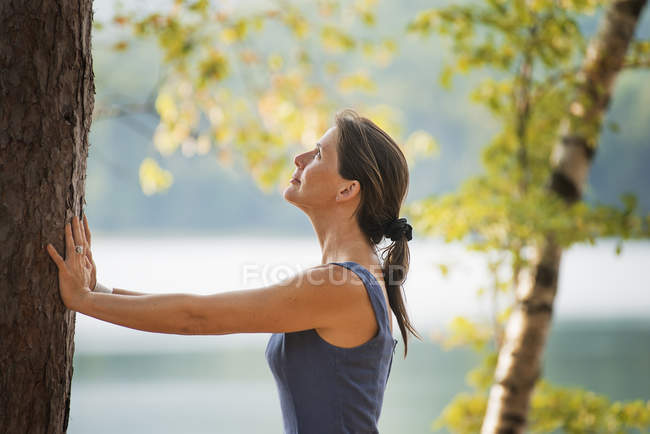 Woman leaning against a tree. — Stock Photo