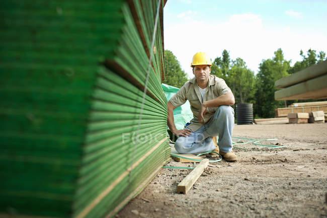 Mann sitzt neben Holzplanken — Stockfoto