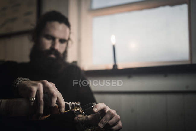 Uomo che si siede da solo con whisky — Foto stock