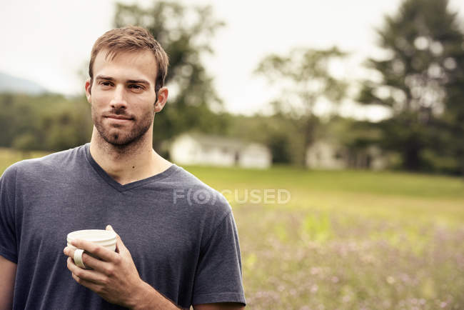 Man holding a coffee cup standing in a field — Stock Photo