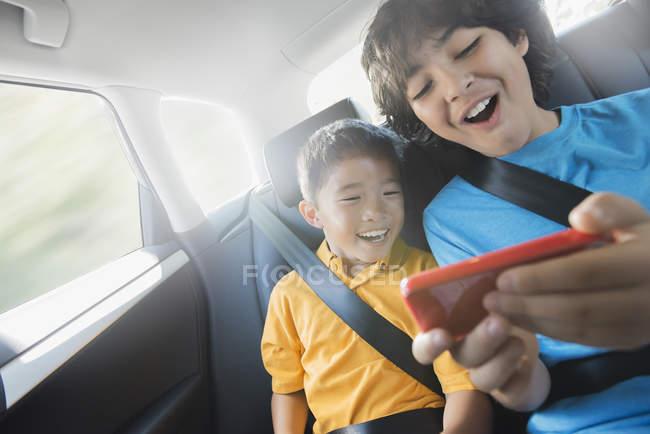 Дети, играть в игры на смартфон — стоковое фото