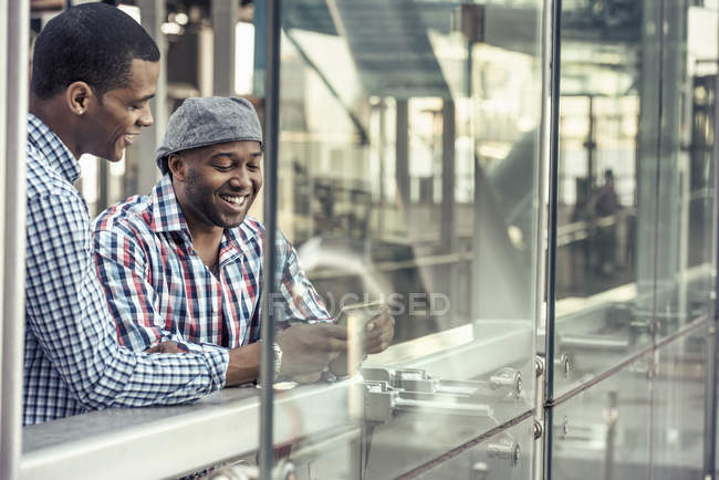 Men side by side looking at digital tablet — Stock Photo