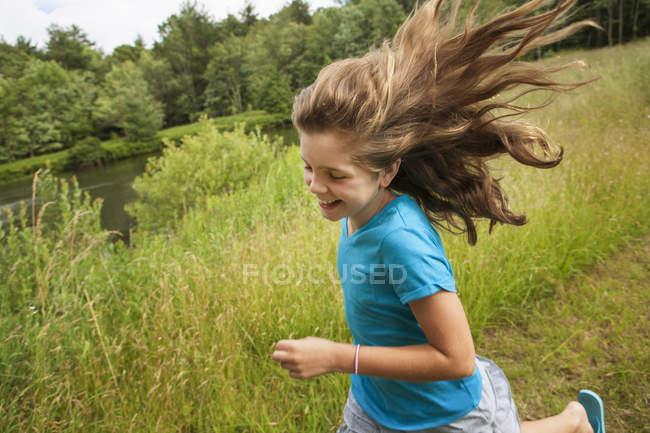 Chica corriendo a lo largo de un camino junto a un lago - foto de stock