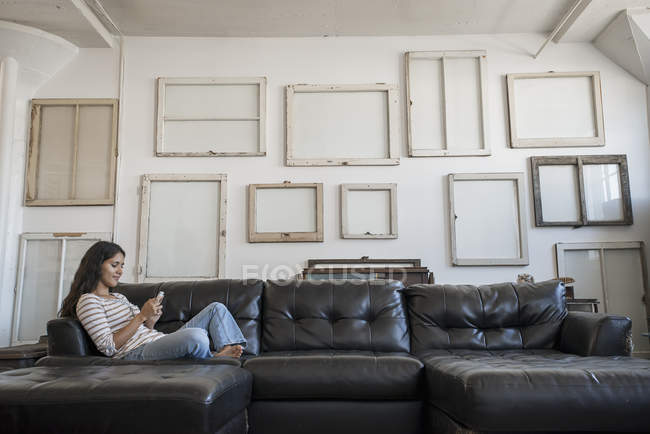 Woman sitting on a sofa — Stock Photo