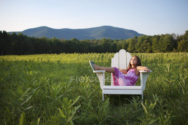 Giovane ragazza seduta sulla sedia — Foto stock