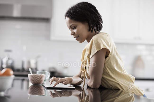 Женщина с помощью цифрового планшета на кухне — стоковое фото