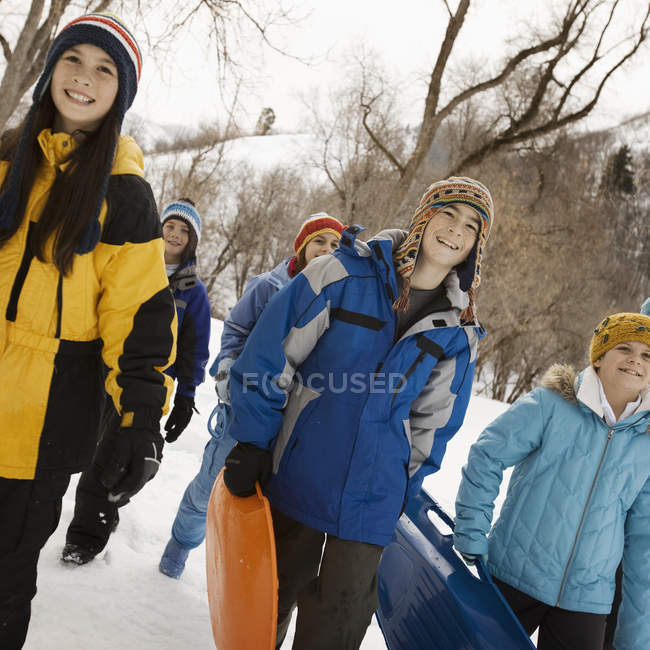 Children carrying sledges across the snow. — Stock Photo