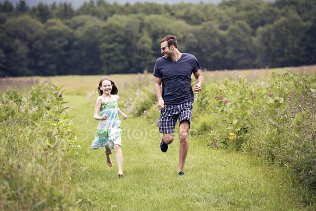 Hombre y niño corriendo por el prado - foto de stock