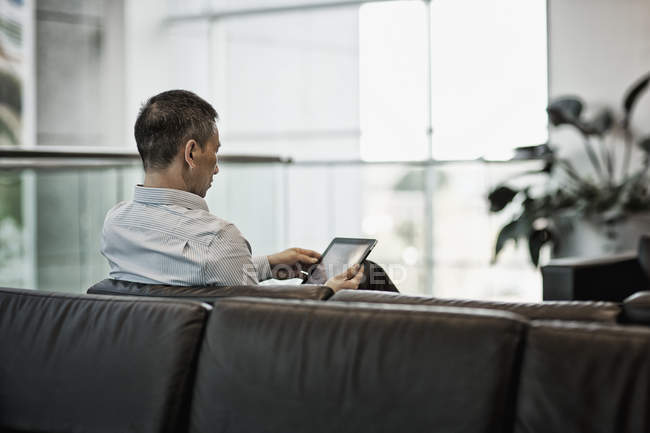 Man seated using a digital tablet — Stock Photo