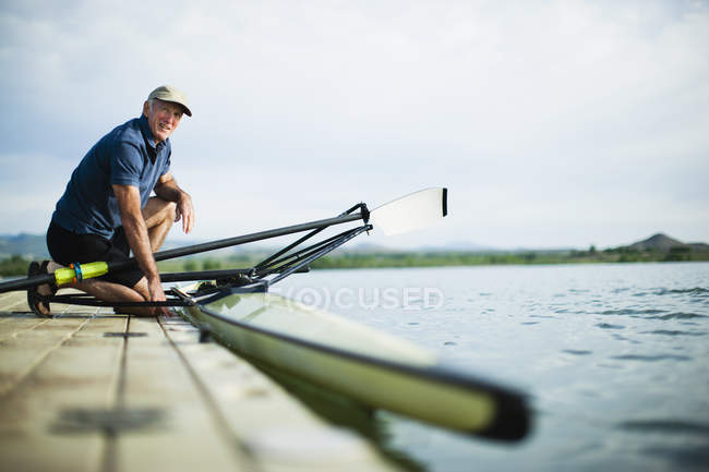 Man on jetty preparing a rowing boat — Stock Photo