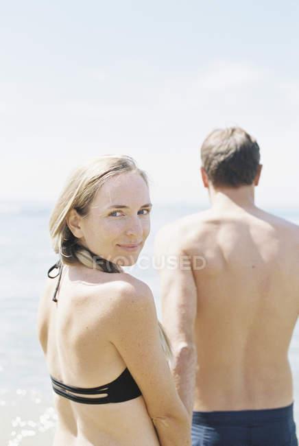 Casal em roupa de banho junto ao oceano — Fotografia de Stock