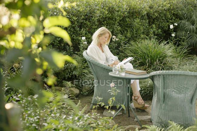 Donna seduta in una sedia di vimini in un giardino — Foto stock
