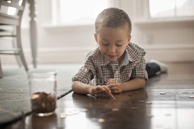 Мальчик играет с монетами — стоковое фото