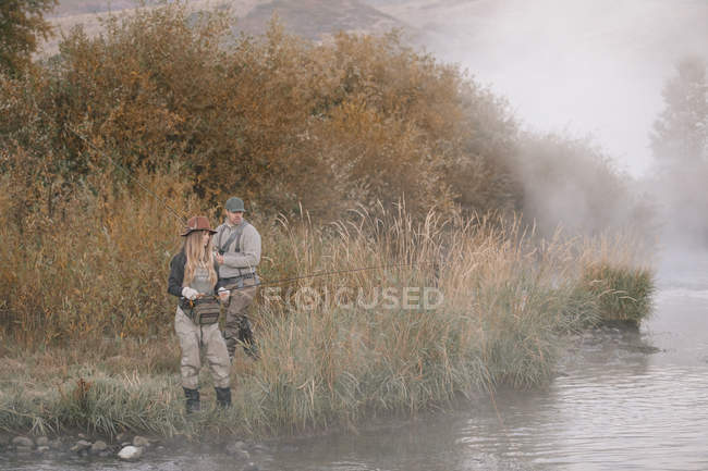 Couple standing on a riverbank, fishing. — Stock Photo