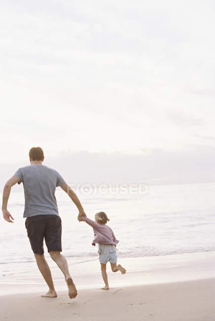Чоловік грає на піщаному пляжі з дочкою — стокове фото