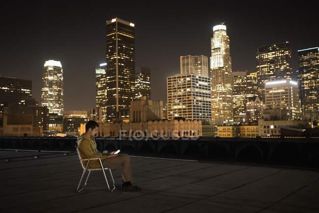 Hombre sentado en una azotea - foto de stock