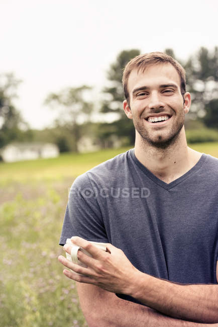 Hombre sosteniendo una taza de café en un campo - foto de stock
