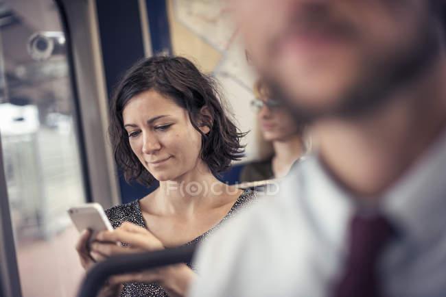 Mulher em um ônibus olhando para celular — Fotografia de Stock