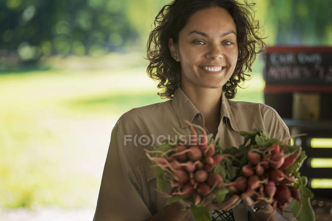 Woman carring bunches of radishes — Stock Photo