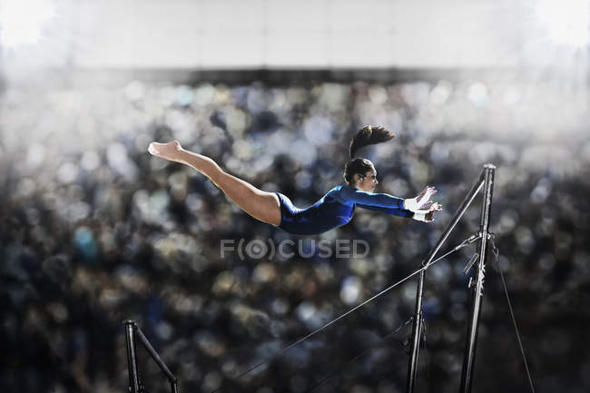 Young woman performing on parallel bars — Stock Photo