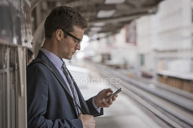 Businessman on a station platform — Stock Photo