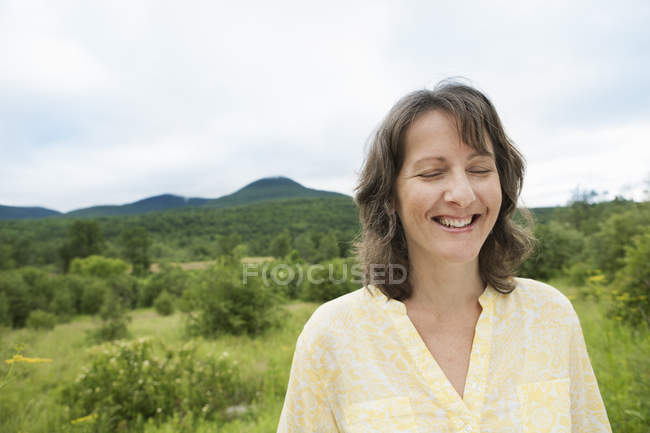 Mulher em campo aberto, por uma montanha — Fotografia de Stock