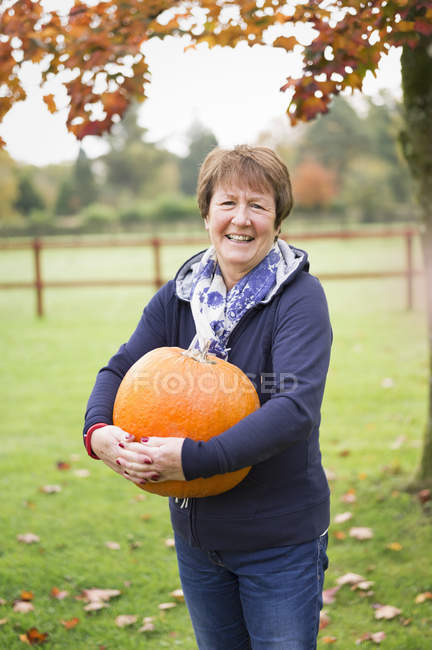 Woman holding a large orange pumpkin. — Stock Photo