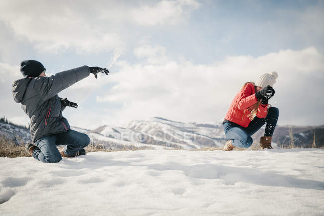Snowball fight between a brother and sister. — Stock Photo