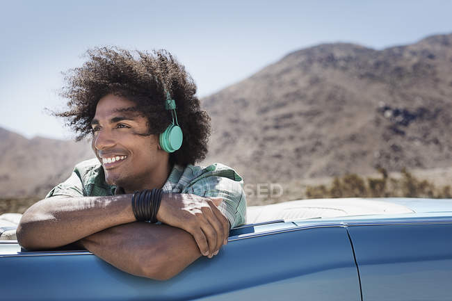 Uomo con cuffie musicali in auto — Foto stock