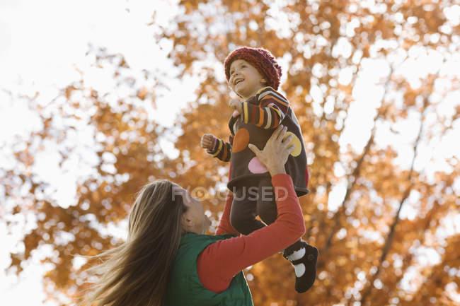 Madre sollevare figlia in aria — Foto stock