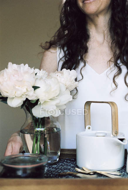 Woman carrying a tray with teapot and flowers — Stock Photo
