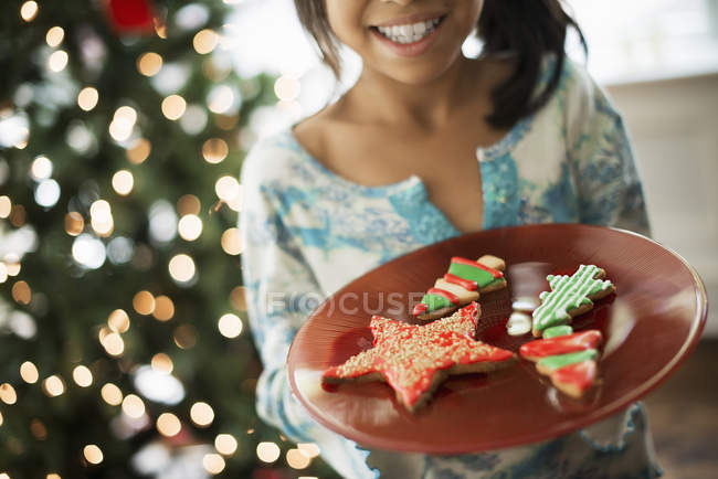 Chica sosteniendo la placa de las galletas de Navidad - foto de stock