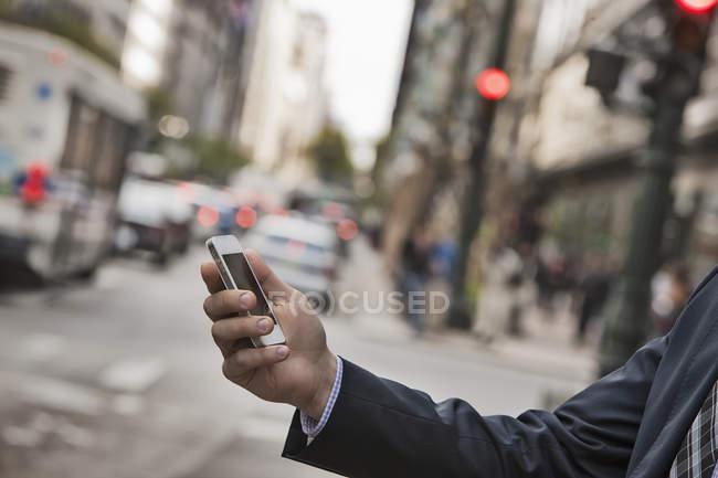 Uomo d'affari che controlla il telefono in strada — Foto stock