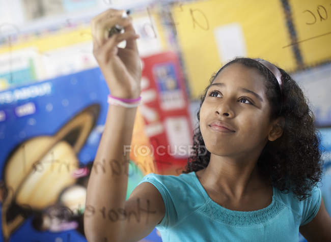 Girl writing with a pen on a board — Stock Photo