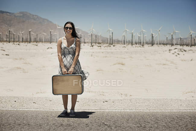 Woman with a suitcase on the edge of the highway. — Stock Photo