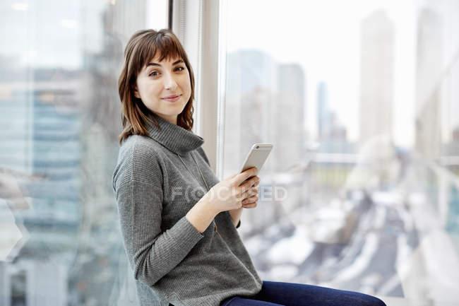 Mujer sosteniendo un teléfono inteligente - foto de stock