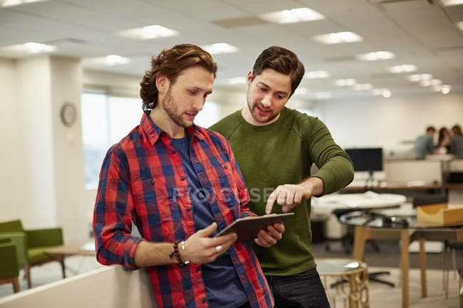 Men looking at a digital tablet — Stock Photo