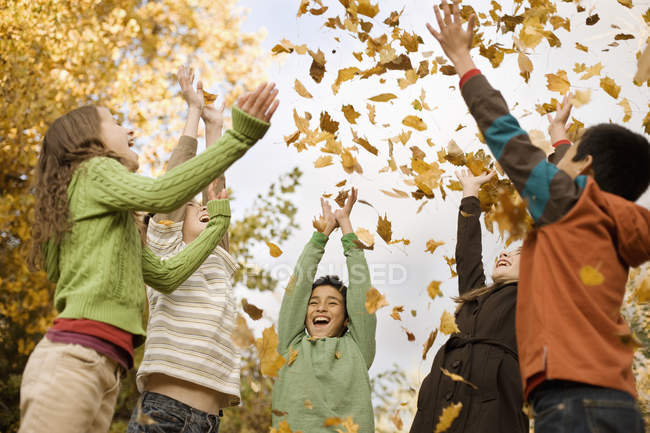 Children throwing fallen autumn leaves — Stock Photo