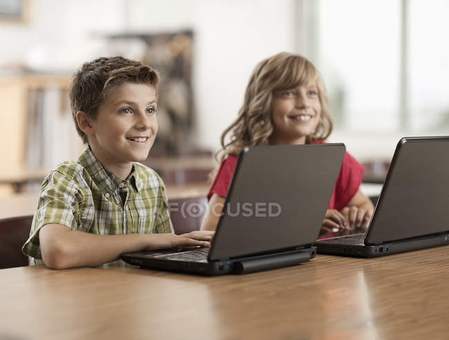 Two children using a laptop computer — Stock Photo