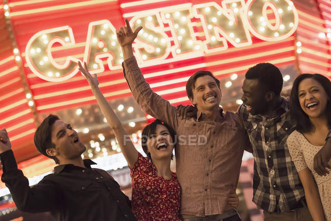 People under a bright neon Casino sign. — Stock Photo