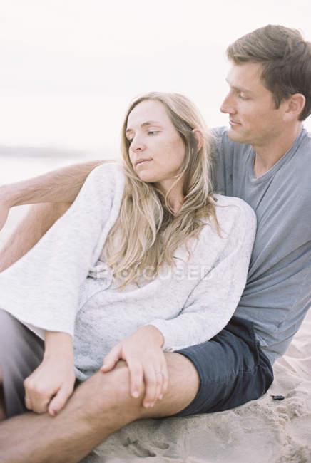 Coppia seduta vicino su una spiaggia — Foto stock