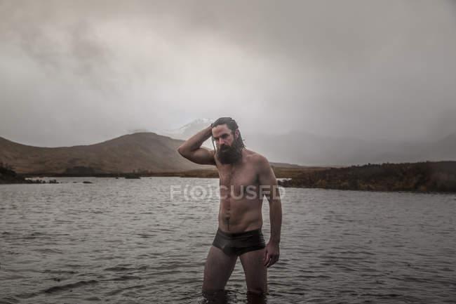 Homme debout cuisse profonde dans la mer — Photo de stock