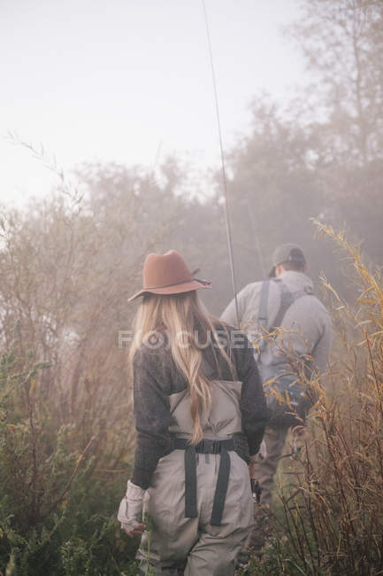 Couple on riverbank with fishing gear. — Stock Photo