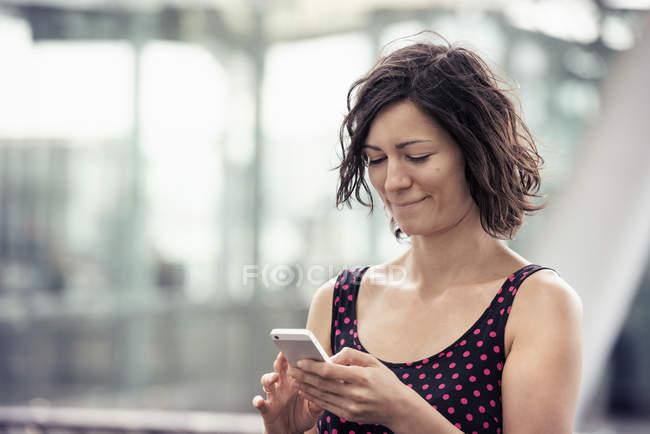 Mulher em uma rua com seu telefone celular — Fotografia de Stock